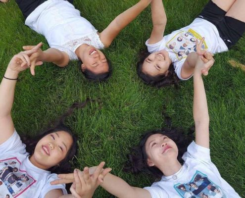 Four teenaged girls laying in grass, hands linked.